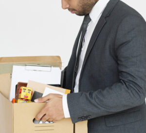 man in suit carrying a box with his personal belongings